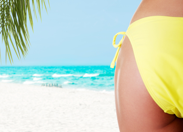 Image of a woman's butt and thigh wearing yellow bikini bottoms