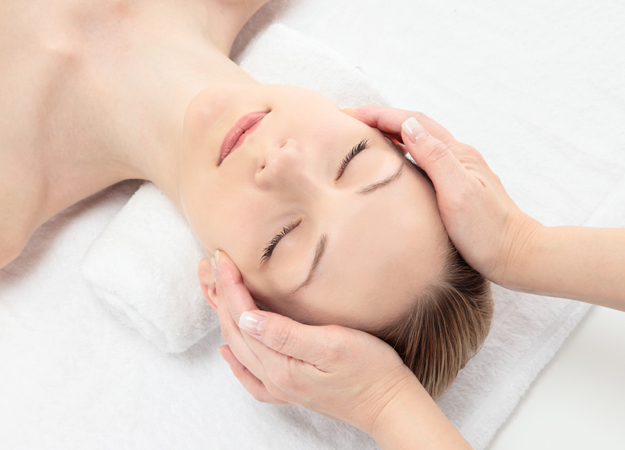 Image of a woman getting a head massage at a spa