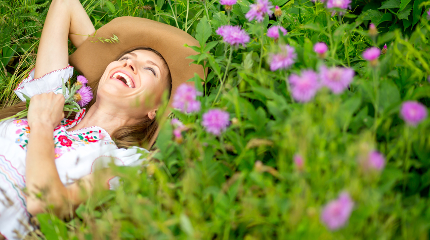 5 Ways to Look Younger This Year - Image of a woman smiling while laying on the ground surrounded by flowers