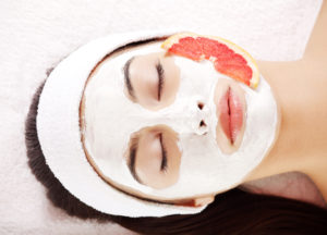 Image of a woman getting an organic facial with a slice of grapefruit on her cheek