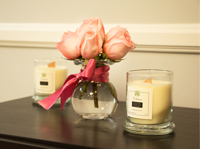 Image of flowers in a vase and two All Natural Soy Candles by The Wax Shop