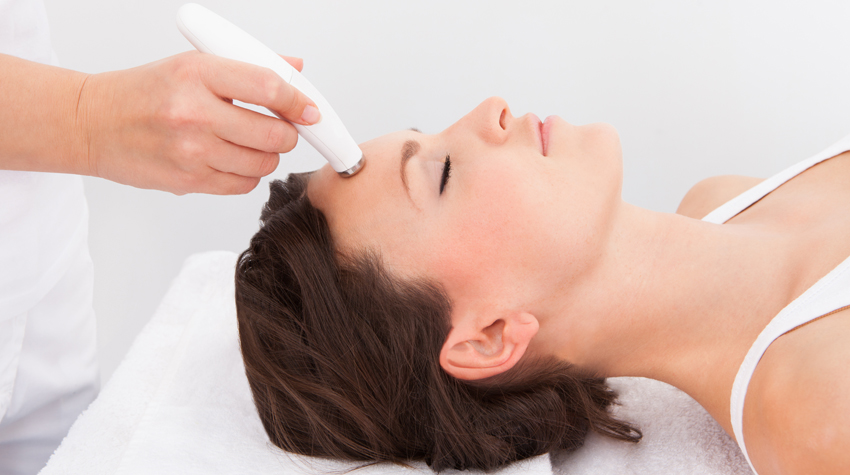 What Is a Facial? - Image of a brunette woman getting a microdermabrasion procedure done